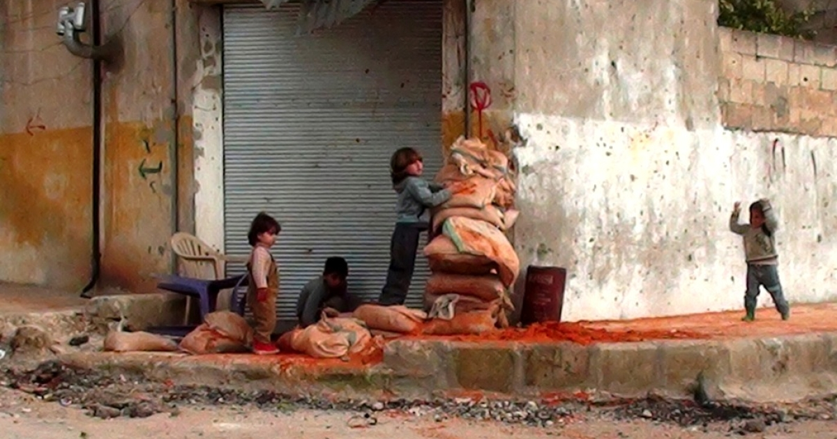 Syrian children hide behind sand bags on the street in the central town of Rastan, near Homs, on March 13, 2012. The political unrest and international sanctions have crippled the Syrian economy.</p>