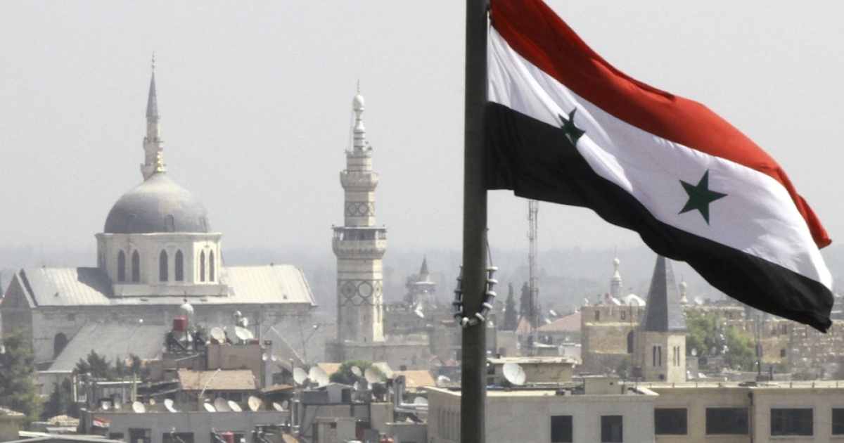 The Syrian flag flutters above Damascus on September 20, 2012.</p>