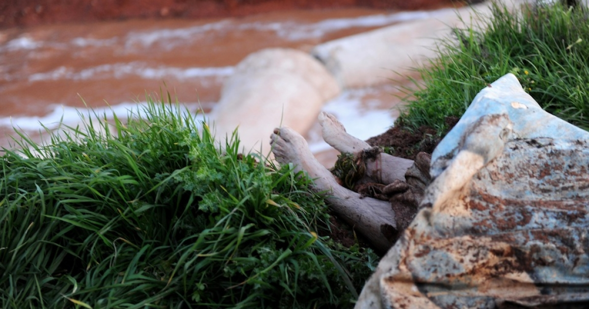 The feet of an unidentified corpse lie near a water canal following an assault by Syrian security forces in Idlib in northwestern Syria on February 18, 2012. AFP/Bulent Kilic</p>