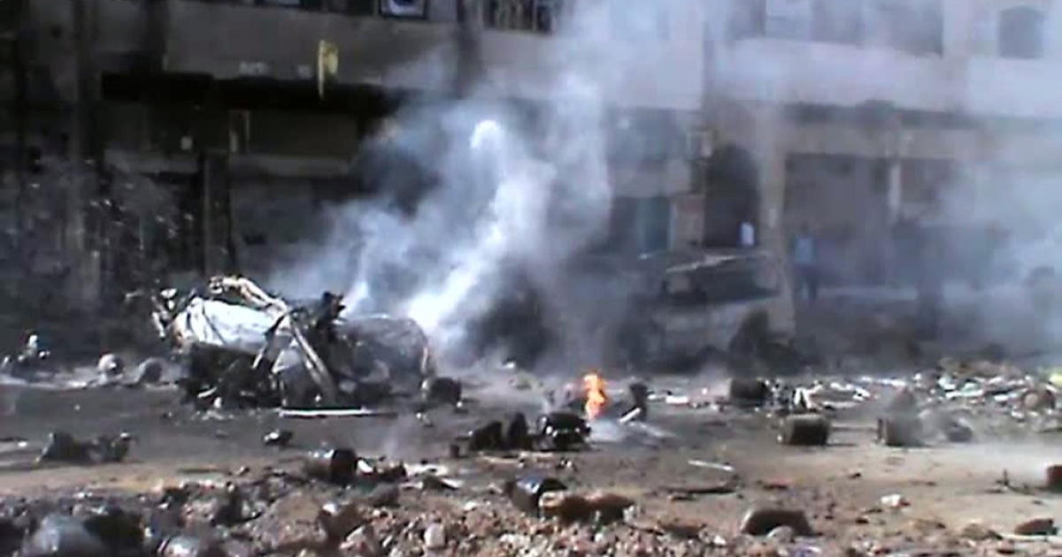 This image grab of footage uploaded on YouTube on March 20, 2012 allegedly shows a burning vehicle and gas cylinders, mainly used for cooking, strewn across a street after a mortar shell struck a gas depot store in the central restive Syrian city of Homs.</p>