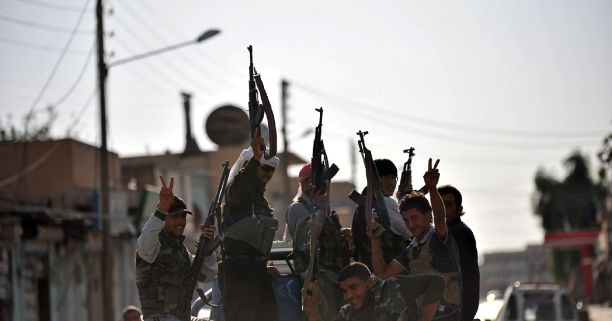 Syrian rebels make victory signs as they patrol a street in the town of Tal Abyad near the border with Turkey on October 5, 2012. Turkey's Prime Minister Recep Tayyip Erdogan again warned Syria it would pay a big price for further attacks, two days after a deadly cross-border shelling.</p>