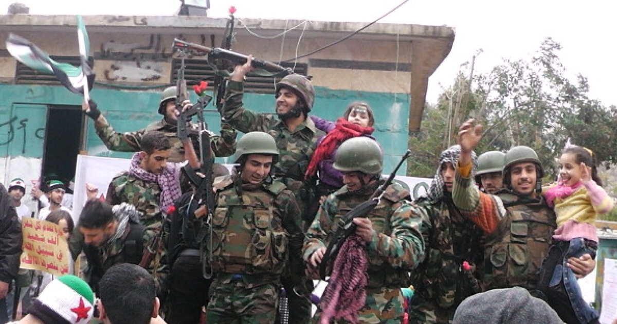 Syrian soldiers who defected join protesters in the al-Khaldiya neighborhood of the restive city of Homs on January 26, 2012. The Britain-based Syrian Observatory for Human Rights said the army launched an offensive on Thursday evening in the Karm al-Zeitoun district of Homs, killing 26 civilians, including nine children, and wounding dozens.</p>