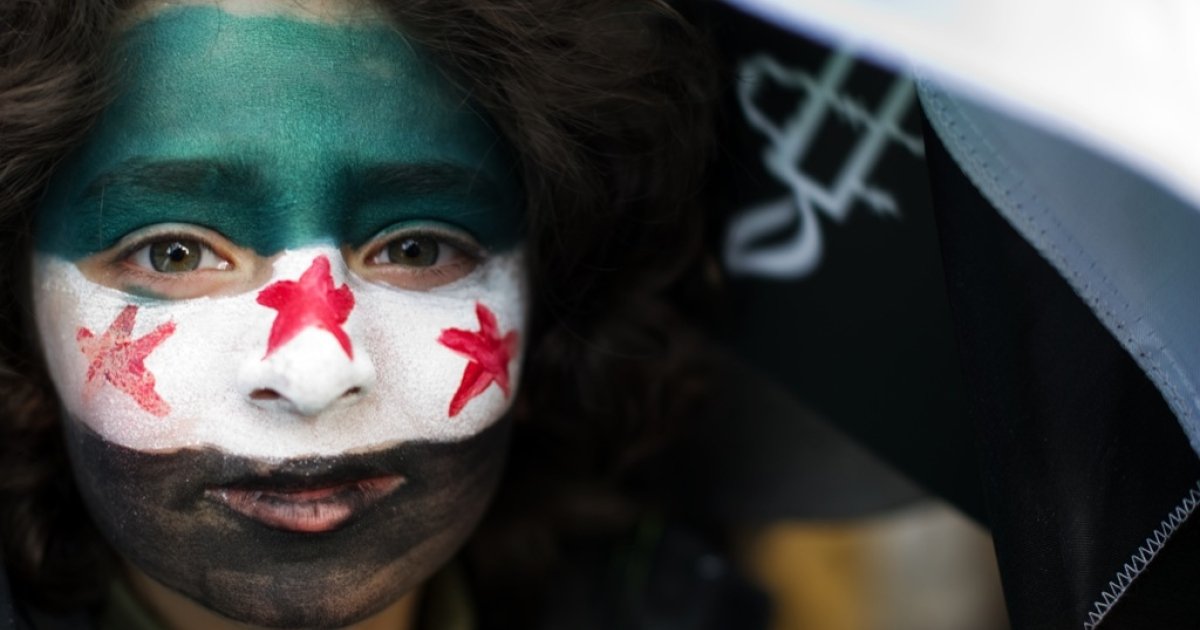 A child with the former flag of Syria painted on his face joins in with the Amnesty International rally in Trafalgar Square, central London on February 11, 2012. The protest was part of an international day of action to show solidarity with protesters in the Middle East and North Africa who are demanding reforms and greater respect for human rights.</p>