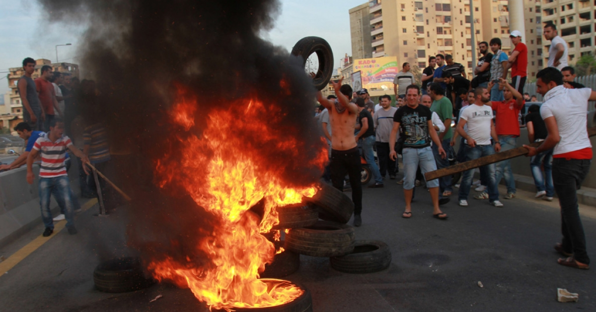 Shiite Muslim youths set tires on fire to block the entrance to Beirut's suburbs in protest against the kidnapping in Aleppo, Syria of 13 Lebanese Shiite pilgrims returning home from a pilgrimage in Iran on May 22, 2012.</p>