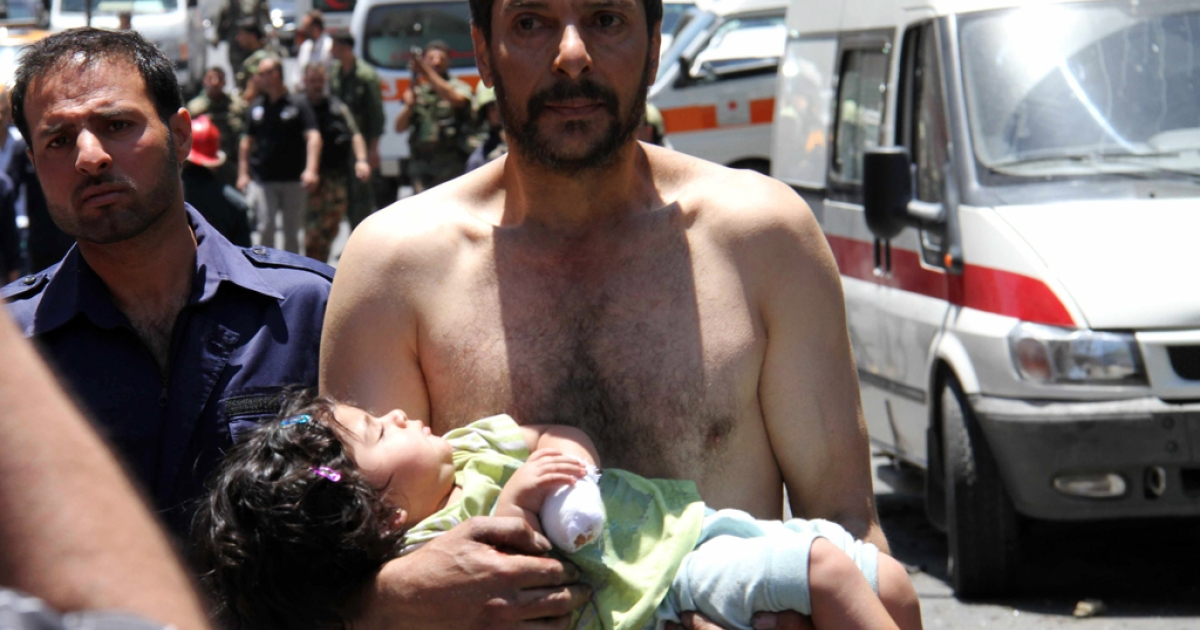 A Syrian man carries a wounded girl next to Red Crescent ambulances following an explosion that targeted a military bus near Qudssaya, a neighborhood of the Syrian capital, on June 8, 2012.</p>