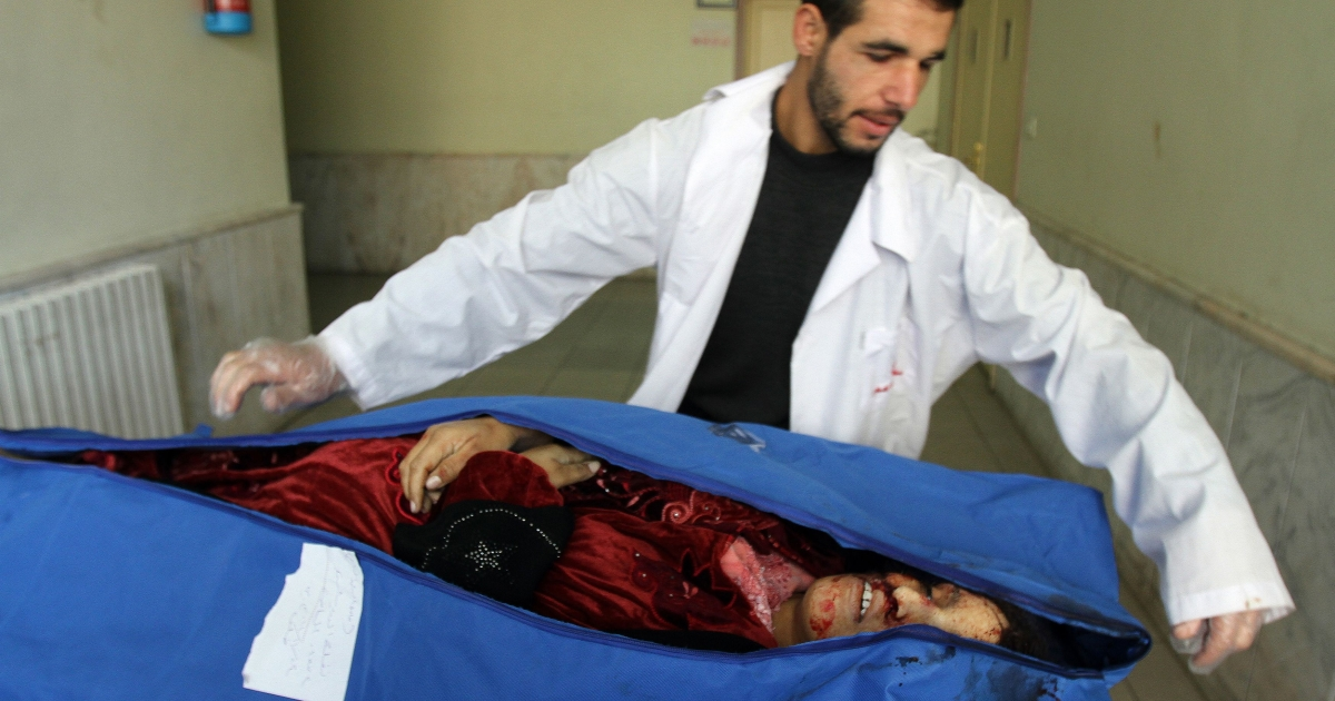 A Syrian medic shows the body of Nafla al-Darwish, a 37-year-old and seven-month pregnant woman who was reportedly gunned down in Bayada neighbourhood, at a hospital in the flashpoint city of Homs on November 25, 2011.</p>