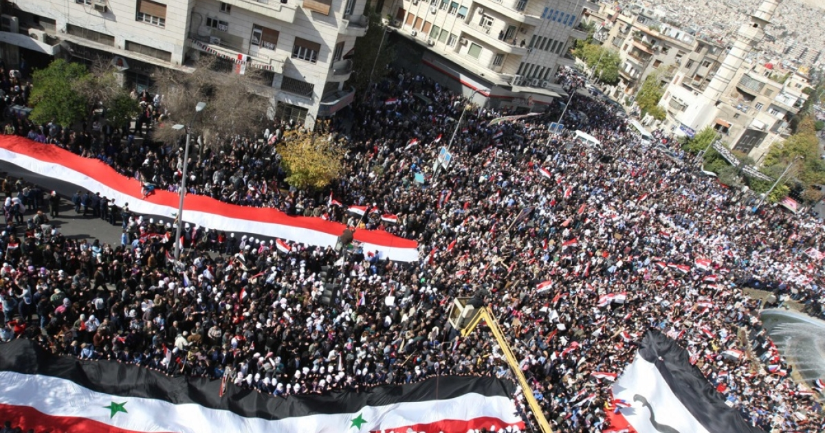 Huge national flags are seen as Syrian's rally to show their support for their President Bashar al-Assad in the capital in Damascus on November 13, 2011, a day after the Arab League suspends Syria until President Bashar al-Assad implements an Arab deal to end violence against protesters, calling for sanctions and transition talks with the opposition.</p>