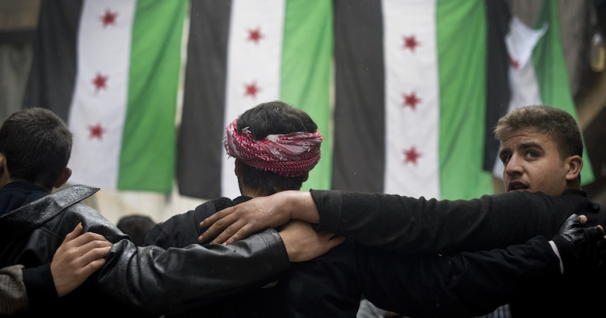 Opposition rebel fighters take part in a demonstration against the Syrian regime n the al-Fardos neighborhood of Aleppo on December 7, 2012.</p>