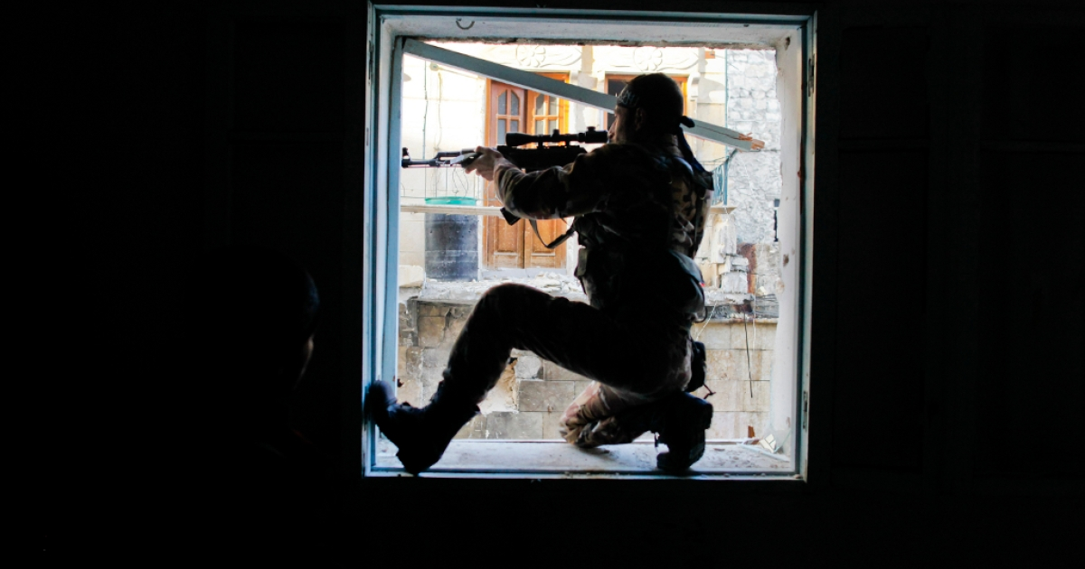 A member of Liwa (Brigade) Salahadin, a Kurdish military unit fighting along side rebel fighters, aims at a regime fighter in the besieged district of Karmel al-Jabl in eastern Aleppo, on December 6, 2012.</p>