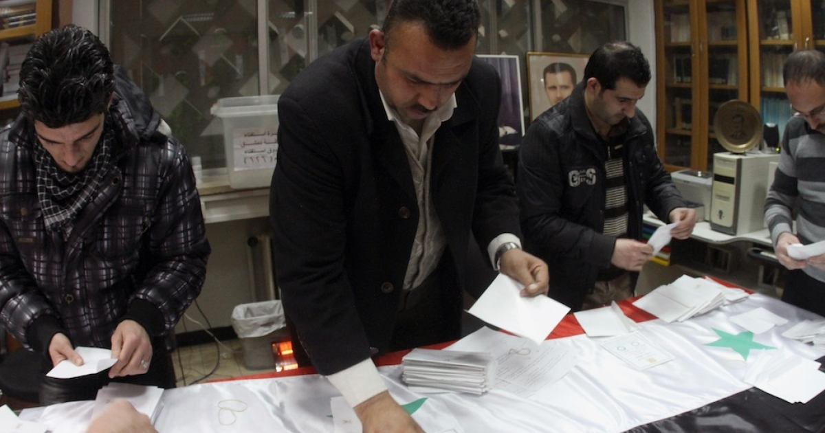 Syrian government workers count ballots at the end of the voting day on the referendum for a new constitution in Damascus on February 26, 2012. ANWAR AMRO/AFP/Getty Images</p>