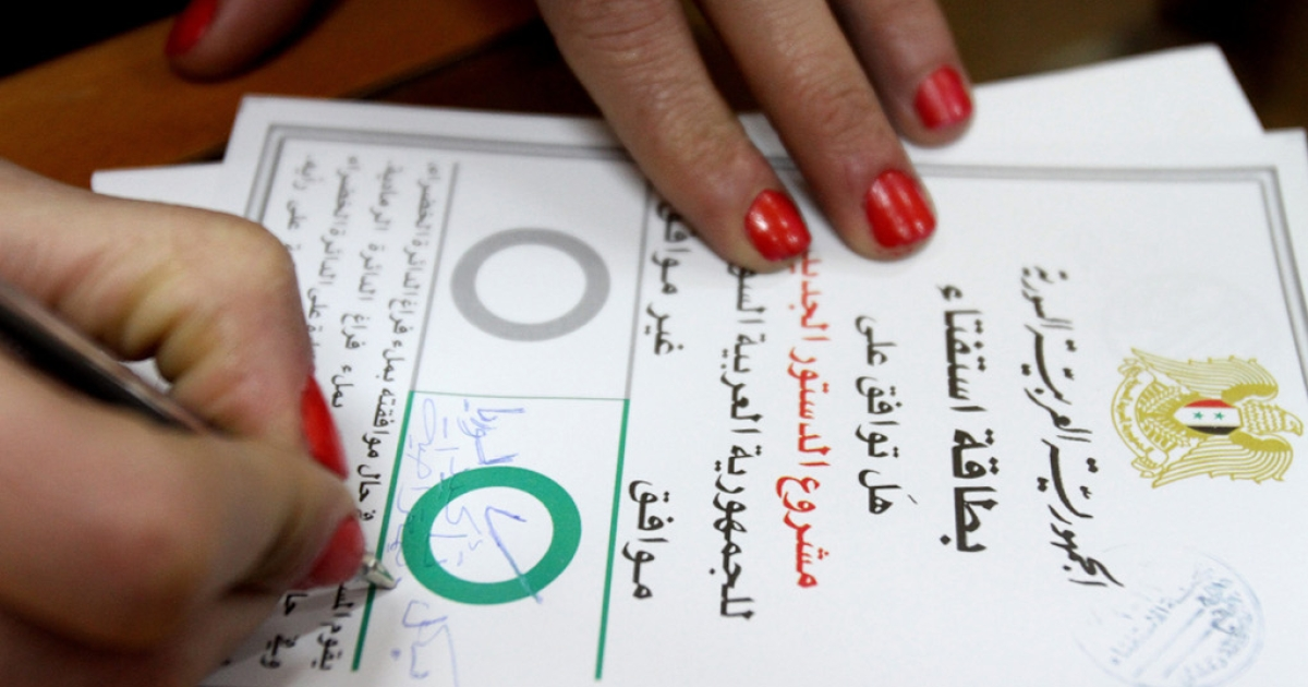 A Syrian woman checks 'Agree' on a ballot card and adds 'Definitely yes for a democratic Syria' before casting her vote on a new constitution at a polling station in Damascus on February 26, 2012.</p>