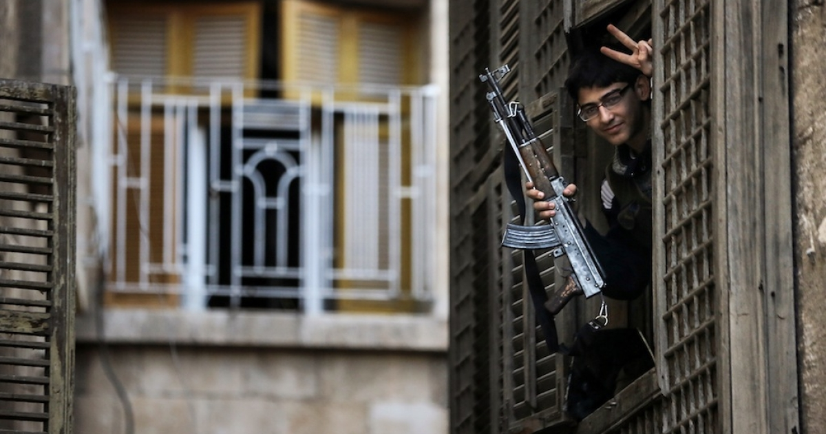 A Syrian university student-turned-rebel makes a victory sign from his post in an ancient building located just 50 metres from the base of Aleppo's citadel in northern Syria on Nov. 8, 2012.</p>
