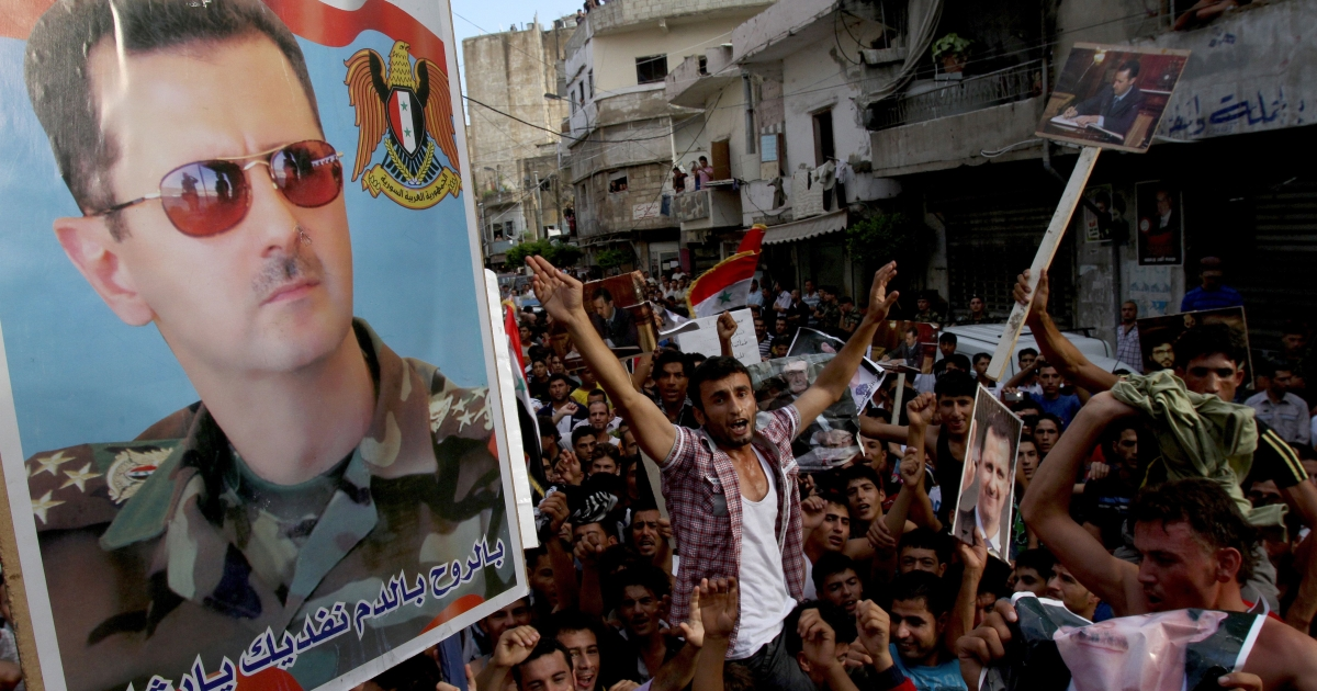 Syrian regime supporters carry pictures of President Bashar al-Assad during a protest in the Nabaa neighborhood of Beirut, Lebanon, Oct. 2, 2011, as Syrian opposition movements announced the formation of a