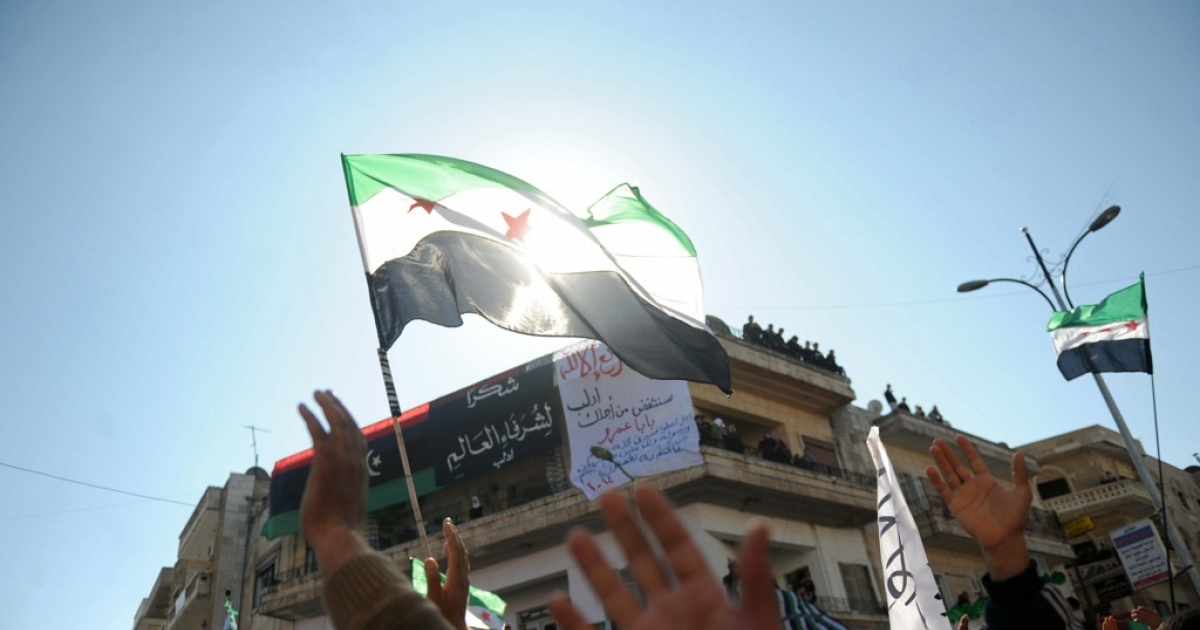 Syrian demonstrators wave the pre-Baath Syrian flags during an anti-regime protest in the centre of Idlib in northwestern Syria. The Assad regime suffered a