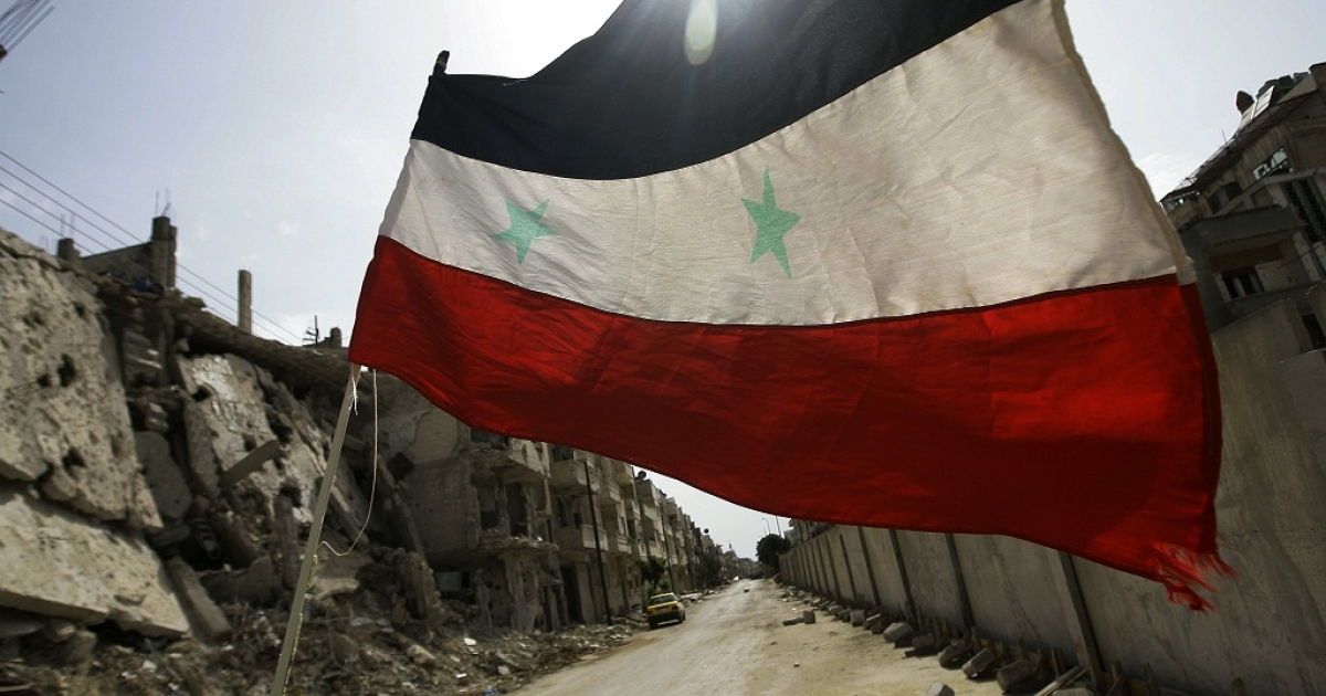 A Syrian flag flutters outside a military barrack in the devastated Bab Amro neighbourhood of the central restive city of Homs on May 2, 2012.</p>
