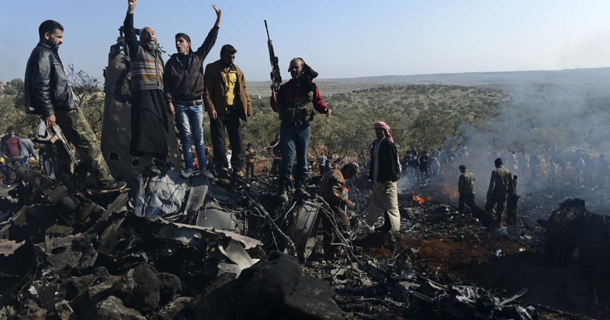 Syrian rebels celebrate on top of the remains of a Syrian government fighter jet which was shot down at Daret Ezza, on the border between the provinces of Idlib and Aleppo, on November 28, 2012.  Syrian rebels captured a pilot manning the fighter jet downed over Daret Ezza in the northern province of Aleppo, witnesses told an AFP reporter in the town.</p>