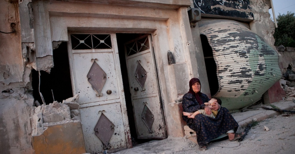 A Syrian woman sits with her grandson outside a damaged building on the main street of the Syrian village of Treimsa, where more than 150 people were killed this week, in the central province of Hama on July 13, 2012. A variety of weapons were used in the attack on Treimsa, with the homes of rebels and activists bearing the brunt, UN observers said.</p>