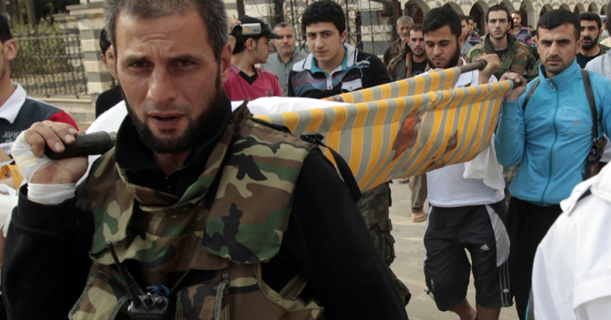 Free Syrian Army members from the al-Faruq Brigade carry the body of one of their comrades to the Khaled Ibn al-Walid mosque for his funeral in the al-Khalidiyah neighbourhood of the central Syrian city of Homs on May 3, 2012. The UN admitted a shaky three-week-old truce in Syria is not holding but said the number of observers would be doubled within days.</p>