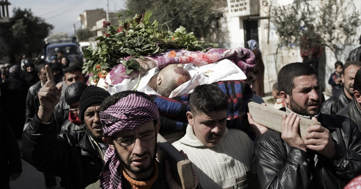 Syrian mourners carry the body of a man who was killed by a shrapnel during his funeral in Qusayr, 15 kms (nine miles) from Homs, on February 28, 2012. Leaders meeting at the European Union summit on March 2, 2012, called upon the Syrian government to end the violence, with British Prime Minister David Cameron saying that the authorities would face
