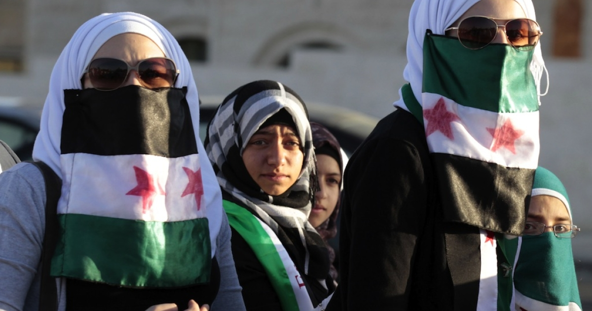 Syrian women living in Jordan use the old Syrian flag adopted by the Syrian opposition groups to cover their mouths during a demonstration against Syria's President Bashar al-Assad and his regime as they gather in front of the prime minister's offices in Amman on June 13, 2012.</p>