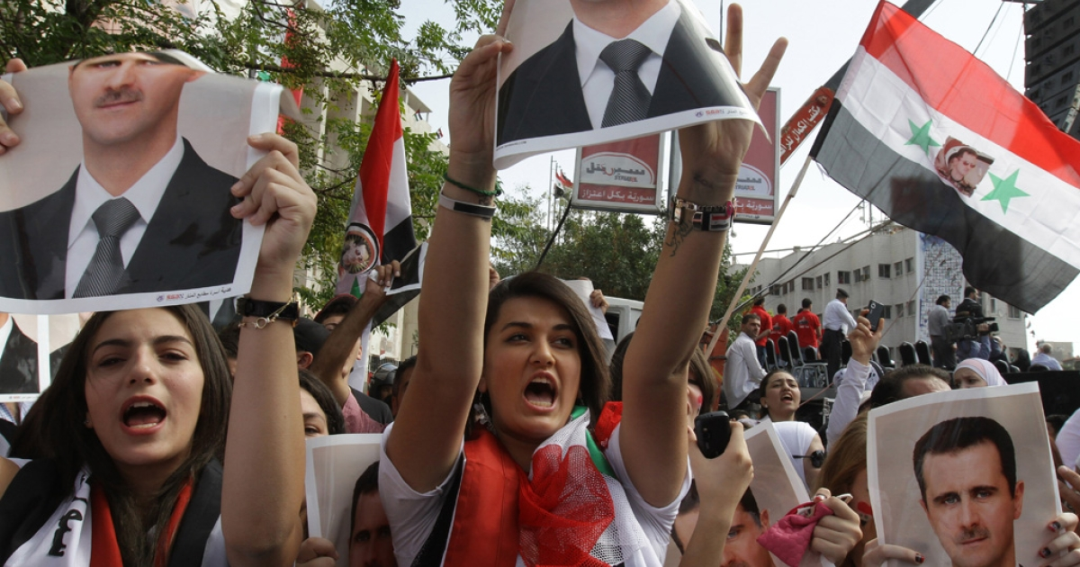 Supporters of Syrian President Bashar al-Assad hold his pictures during a pro-regime rally in Damascus on October 12, 2011. Assad's regime is facing international pressure amid a violent crackdown on anti-government protests that broke out in March across Syria. (LOUAI BESHARA/AFP/Getty Images)</p>