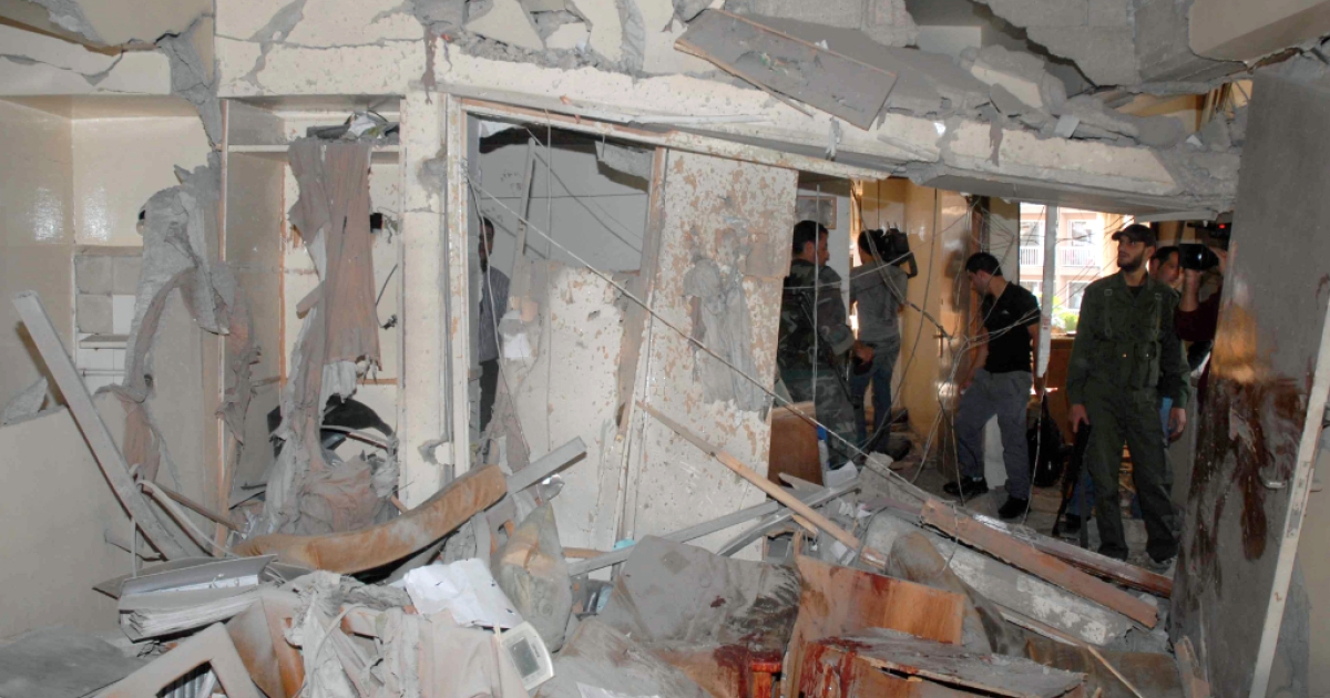 Syrian security members inspect the damage in a building, caused by an explosion near the Dama Rose hotel, in the heart of the Syrian capital Damascus, on November 4, 2012. State news agency SANA said that the blast, which was at the area close to several security centres and Syrian military headquarters, left several people wounded.</p>