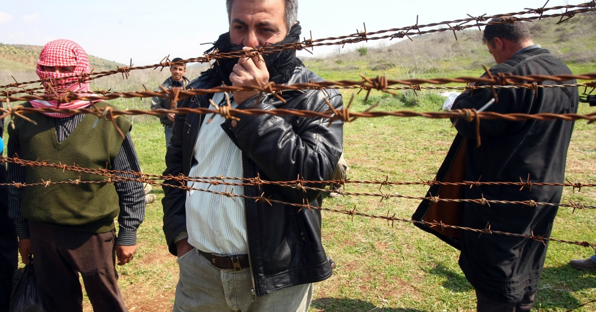 Syrian refugees look through barbed wire today from the Syrian side at the border between Syria and Turkey.</p>