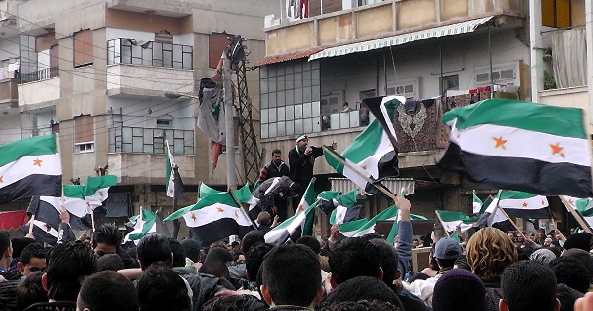 Syrian anti-regime demonstrators wave the former Syrian flags today in the Khalidiya neighborhood, said to be under the control of the Free Syrian Army, in the flashpoint city of Homs.</p>