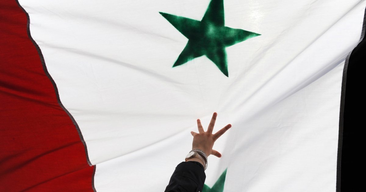 A woman holds up a Syrian flag during a demonstration gathering activists, including Syrians living in Turkey, opposed to Syria's regime of President Bashar al-Assad after the Friday prayers on July 29, 2011 in front of the Syrian consulate in Istanbul.</p>