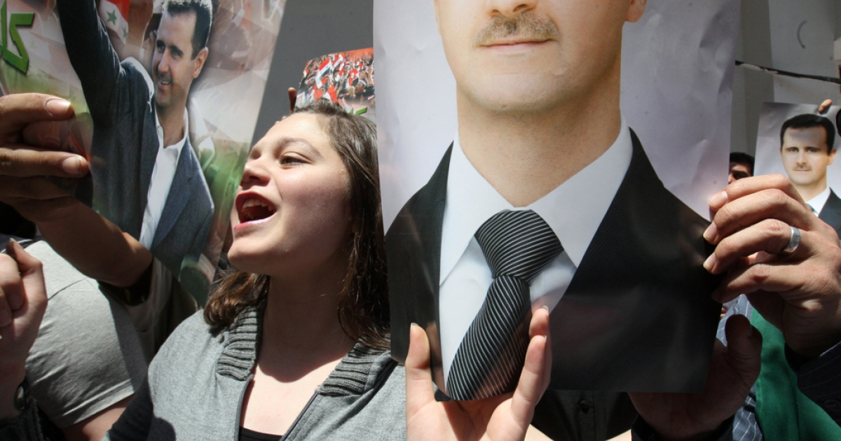 Syrian supporters of President Bashar al-Assad chant pro-government slogans as they wait to cast their vote in the parliamentary elections at a polling station in Damascus on May 7, 2012. Polling stations opened in Syria for the first
