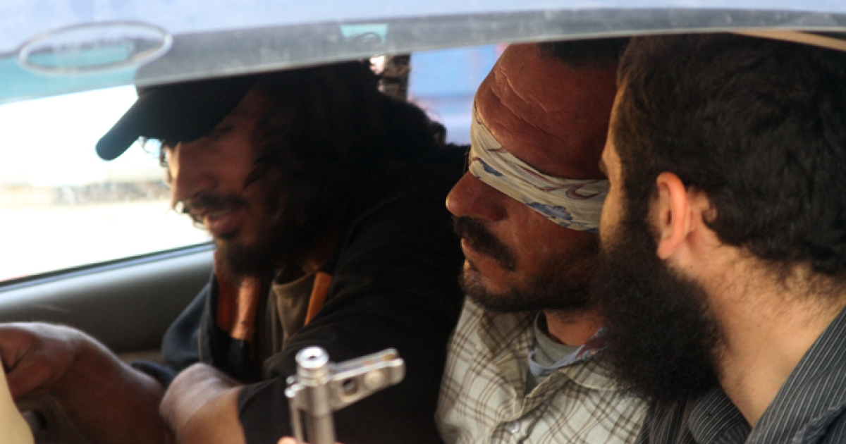 Ahmed Hasseba sits blindfolded in a car that later took him to a rebel base in Jabal al-Zawiya, Syria, where he was imprisoned.</p>