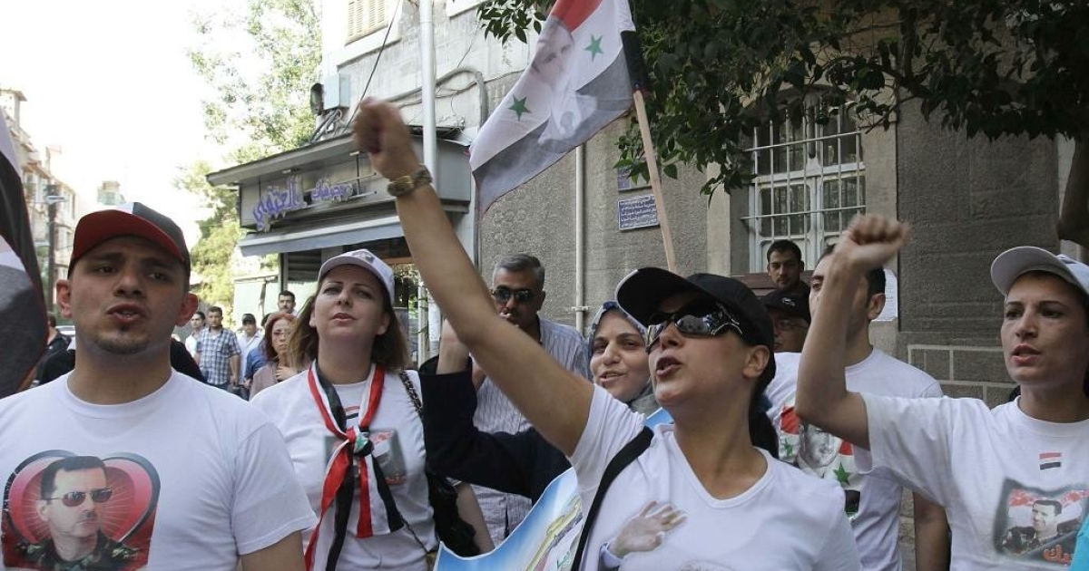 Pro-government protesters gather outside the French Embassy in Damascus, Syria on July 11, 2011.</p>