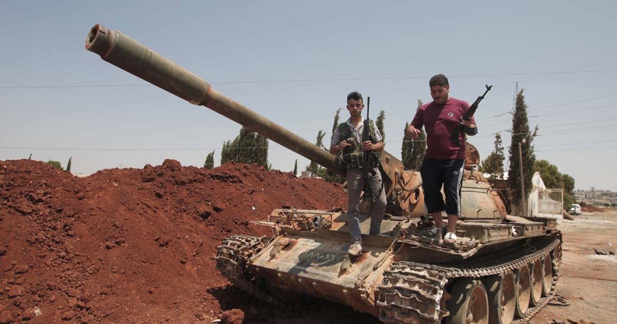 Syrian rebel fighters stand on top of a government tank captured two days earlier at a checkpoint in the village of Anadan, about five kilometres (3.8 miles) northwest of Aleppo, on August 01, 2012.</p>