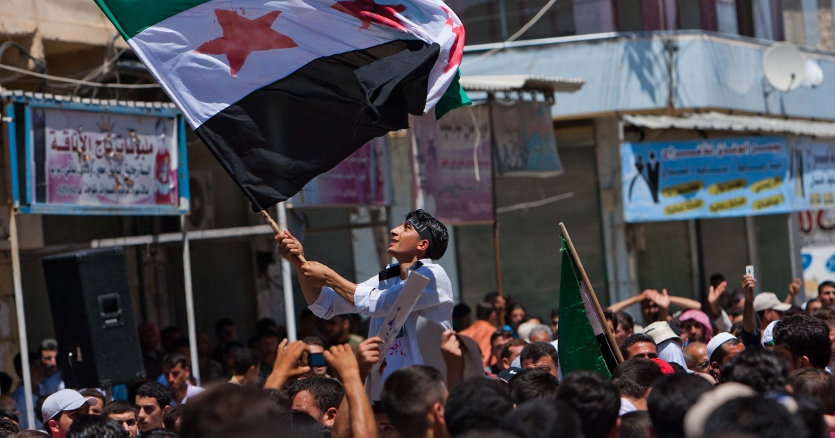 A Syrian youth waves the Syrian revolutionary flag during an anti-government demonstration in the rebel-controlled northern countryside city of Mareh.</p>
