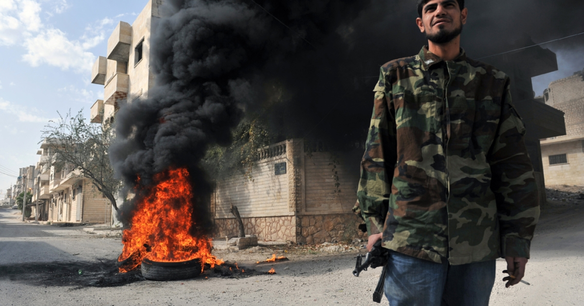 A Syrian rebel stands next to burning tyres set on fire by rebels in order for the black smoke to obscure the vision of regime pilots in the northwestern town of Maaret al-Numan on October 20, 2012. Syrian regime forces and rebels clashed around a besieged army base near the strategic northern town of Maaret al-Numan, an AFP correspondent said.</p>