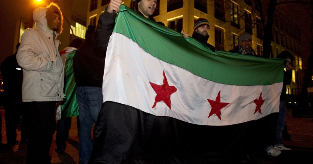 Protesters hold a Syrian flag outside the Syrian embassy in Berlin, Feb. 3, 2012. German police are investigating whether Syrian agents spied on opposition figures in Germany over several years.</p>