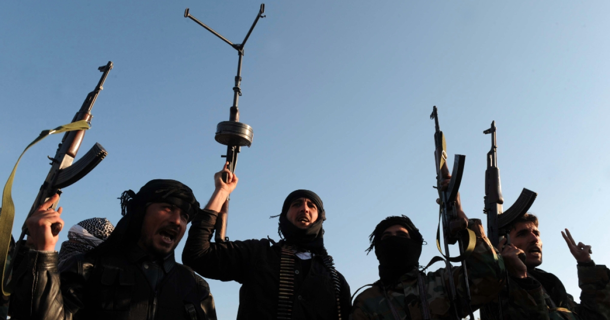 Members of the Free Syrian Army hold up their weapons in Syria's northwest on February 18, 2012.</p>