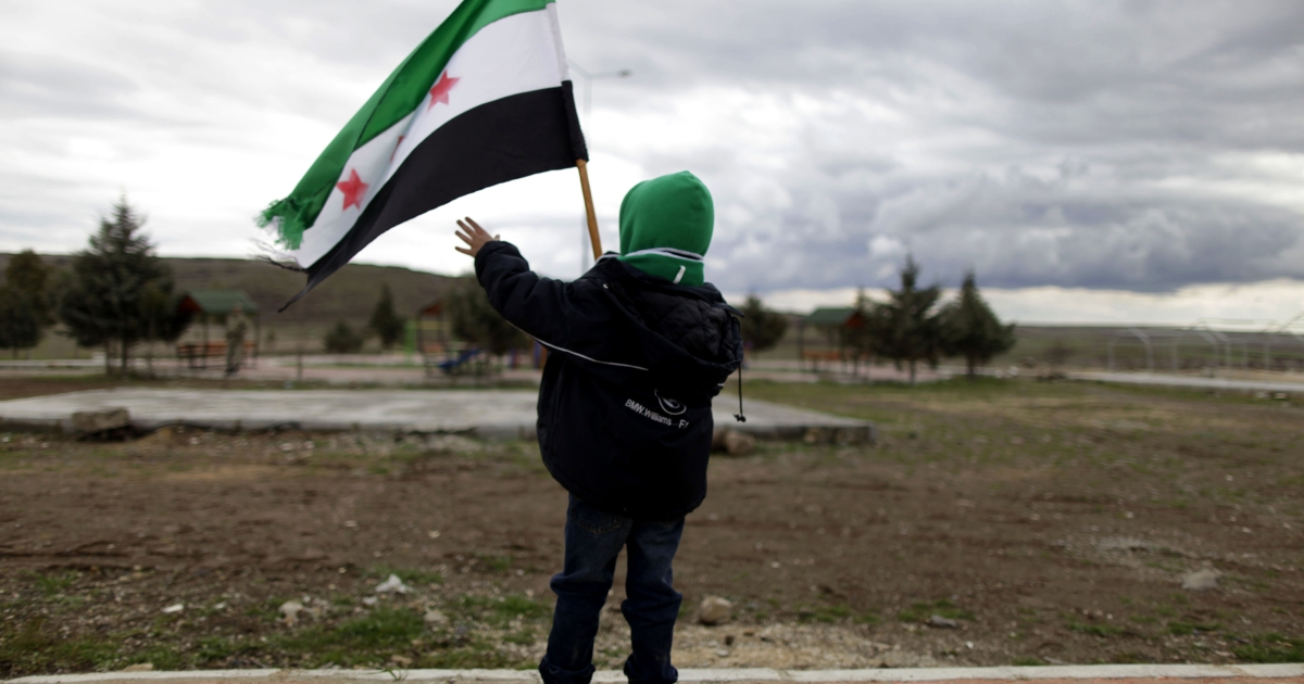 "A boy waving the pre-Baath flag adopted by the Syrian anti-regime opposition is pictured before Turkish police stopped members of a ""Freedom Convoy"" who tried to enter Syria from outside the Turkish city of Kilis on Thursday.</p>"