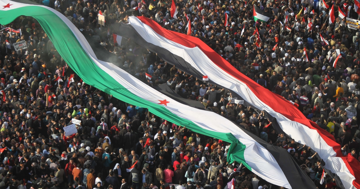 Egyptian protesters hold up giant national and Syrian flags during a rally in Tahrir Square on January 25, 2012, on the first anniversary of the country's revolt against the former regime. AFP PHOTO / KHALED DESOUKI</p>