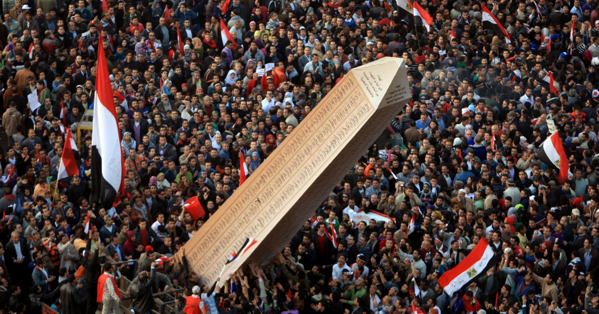 Egyptian protesters carry an obelisk with the names of those killed during last year's uprising, at a huge rally in Tahrir Square on January 25, 2012, marking the first anniversary of the uprising that toppled president Hosni Mubarak as a debate raged over whether the rally was a celebration or a second push for change. AFP PHOTO/MAHMUD HAMS</p>