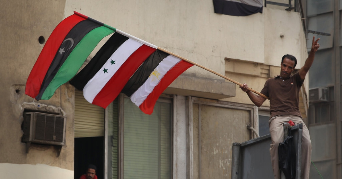 A demonstrator waves an Egyptian, Syrian and Libyan flag in Tahrir Square on May 27, 2011 in Cairo, Egypt. The ruling Supreme Council of the Armed Forces said that there would be no use of violence against protests dubbed 'the Second Revolution of Anger' taking place in Cairo and other cities in Egypt.</p>
