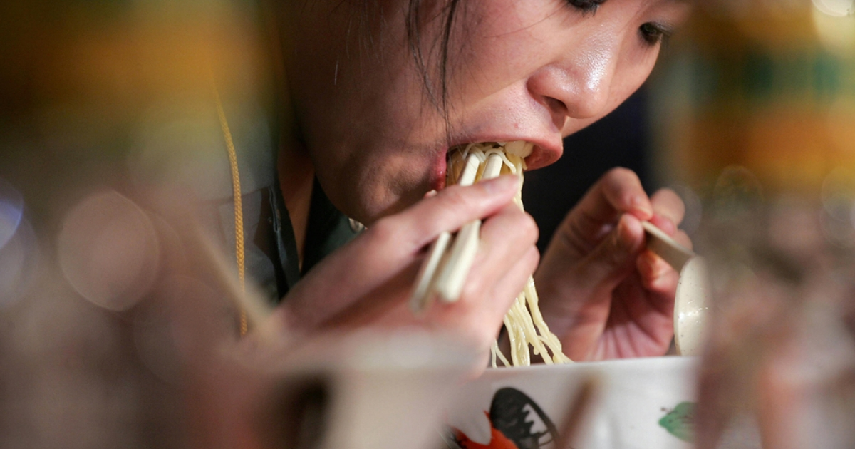 A Chinese woman wolfs down her noodles in Hong Kong.</p>