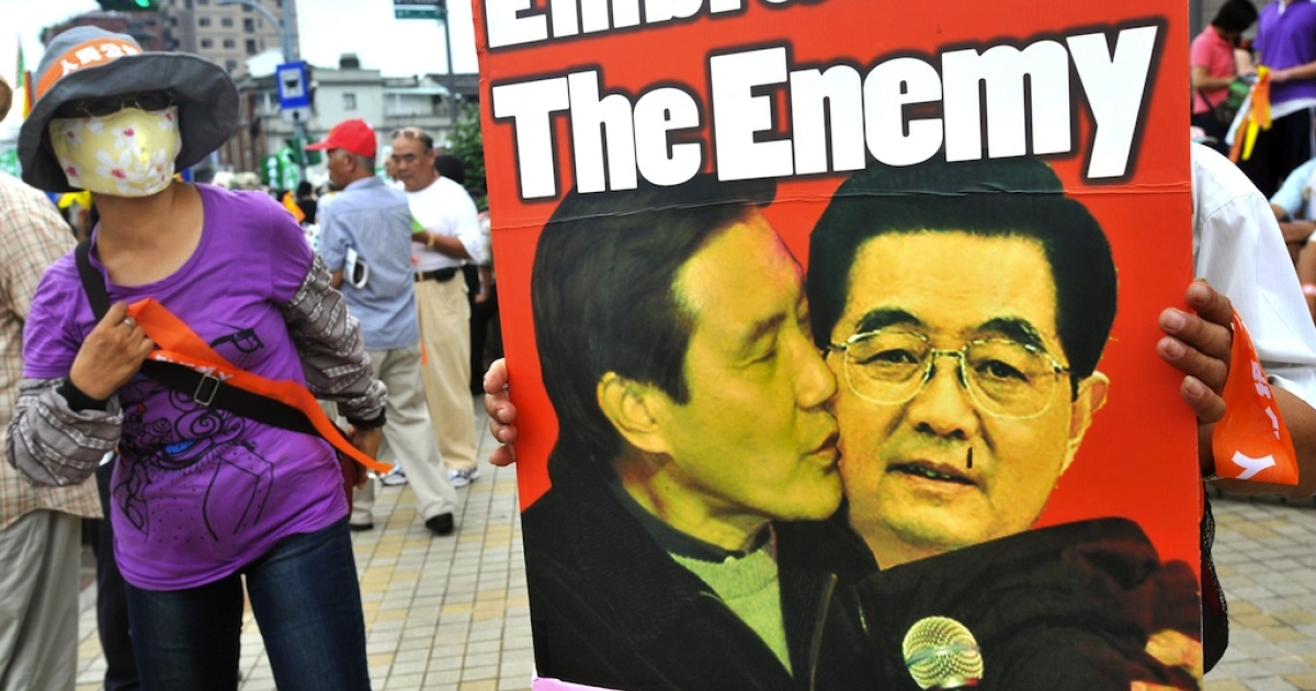 A supporter of Taiwan's opposition Democratic Progressive Party holds a placard reading 'stop embracing the enemy' along with a digitally manipulated photo of Taiwan's President Ma Ying-jeou and Chinese President Hu Jintao during a protest in Taipei on June 26 2010, against a major trade deal to be signed in the coming days with China.</p>
