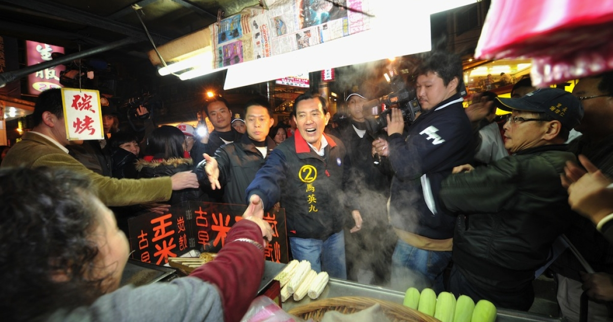 Taiwan President Ma Ying-jeou (C) shakes hands with a food stall worker in Keelung City on Jan. 11, 2012.</p>