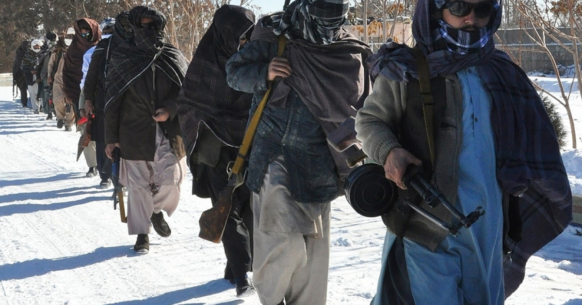 Taliban fighters walk with their weapons after joining Afghan government forces for a ceremony in Ghazni province on January 16, 2012. Some 20 Taliban fighters including a key commander laid down arms and joined the peace process in Ghazni province. The Taliban, ousted from power by a US-led invasion in the wake of the 9/11 attacks, announced earlier this month that they planned to set up a political office in Qatar ahead of possible talks with the United States. AFP PHOTO/Aref Yaqubi</p>