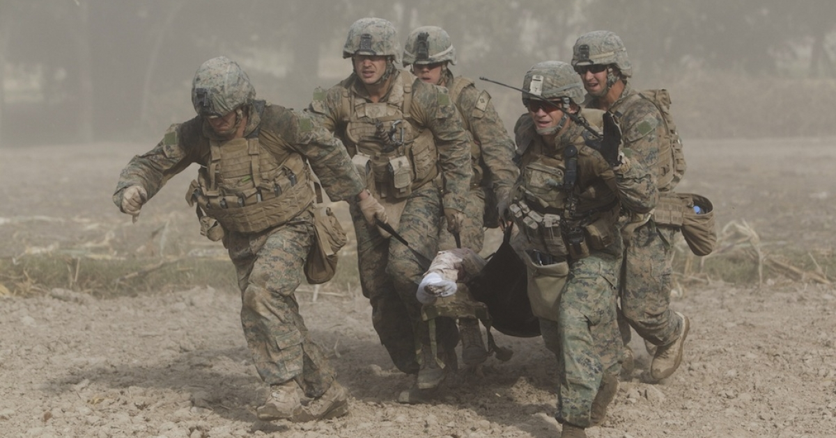 In this picture taken on November 2, 2011 and cleared on December 20,2011 by the US Army , US Marines, through a haze of fine dust kicked up by the helicopter's rotor blades, carry a wounded comrade who was hit by an Improvised Explosive Device (IED) to a medevac helicopter of the US Army's Task Force Lift 'Dust Off', Charlie Company 1-171 Aviation Regiment in Helmand province. The Marine lost his right leg from the knee in the blast.</p>