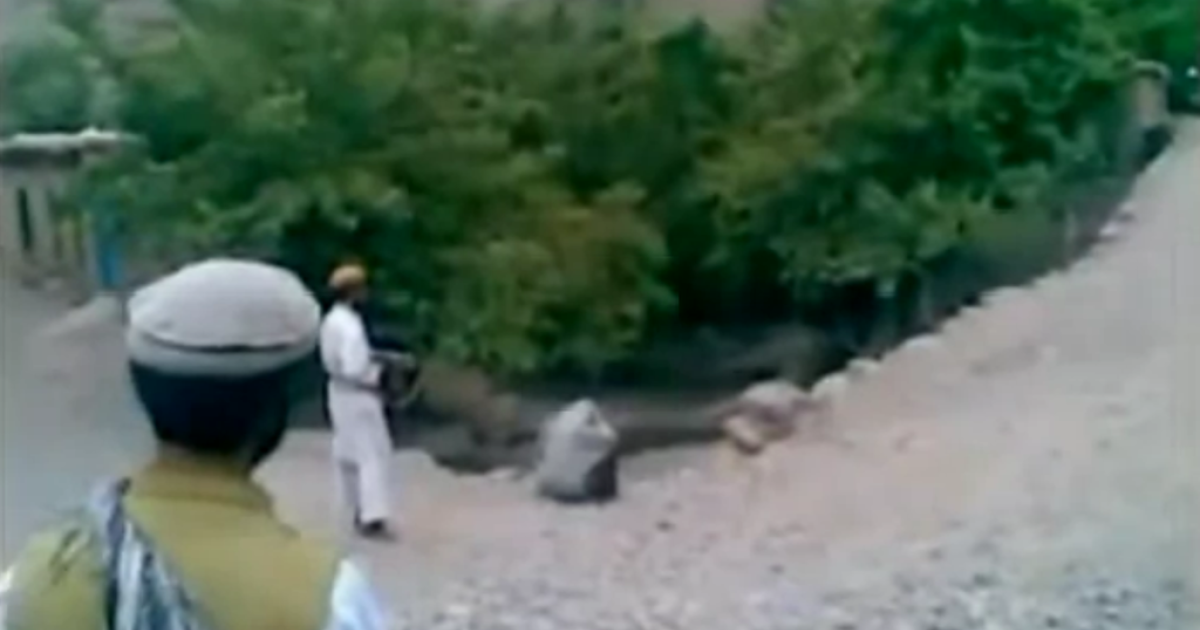 This screenshot shows a member of the Taliban shooting a woman (huddled) at point-blank range, while others look on.</p>