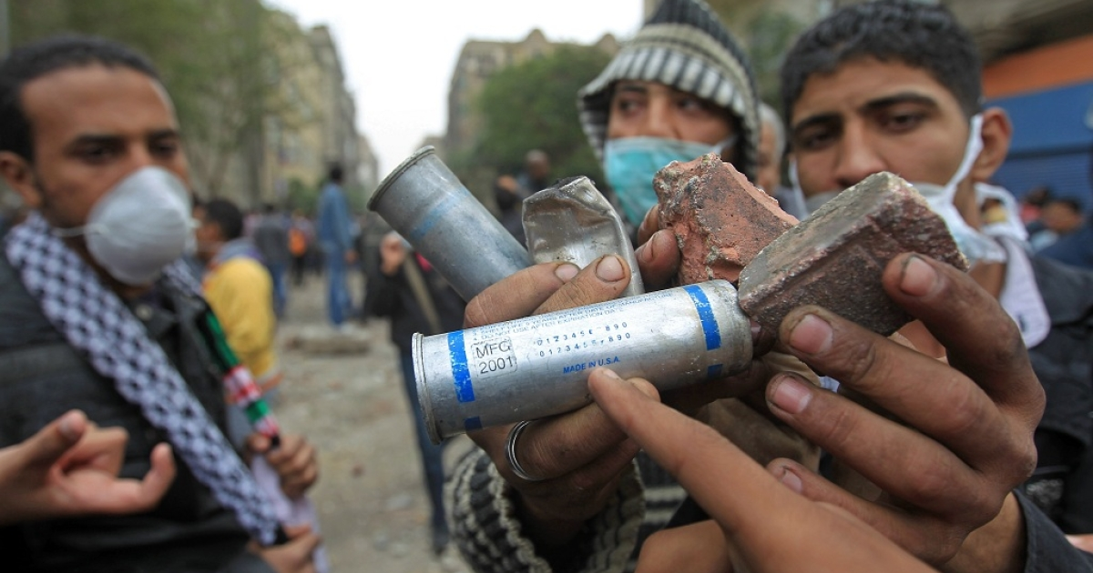 Egyptian protesters point to the 'Made in USA' tag on a tear gas canister during clashes with riot police at Cairo's landmark Tahrir Square on November 20, 2011. Egyptian protesters streamed into the square after a night of deadly clashes that signalled the start of a violent countdown to the first polls since Hosni Mubarak's ouster.</p>