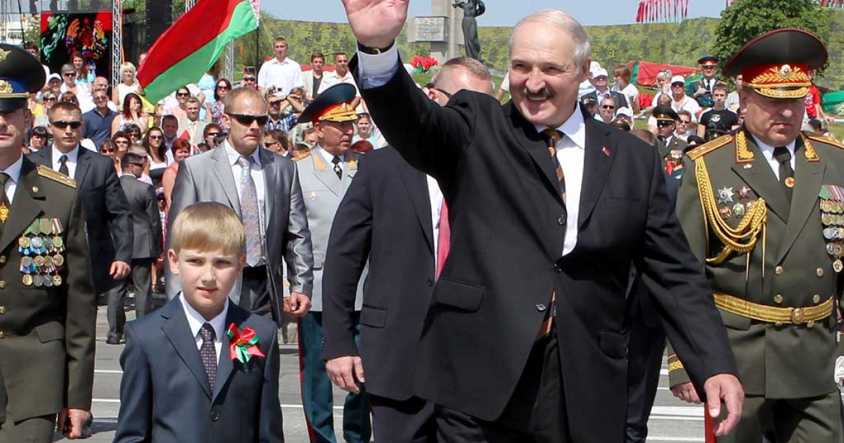 Belarus President Alexander Lukashenko waves as he walks with his son Nikolay while arriving to watch a military parade to mark the nation's Independence Day  in central Minsk, on July 3, 2012.</p>
