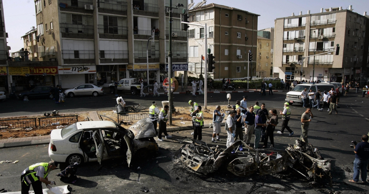 Israeli emergency personnel gather around the scene of a car bomb blast in the Israeli town of Rishon LeZion on Sept. 29, 2006.</p>